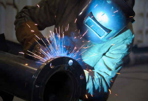 Pipefitting welder in training with mask on working on pipe